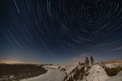 Star trail around the pole star in the night sky. Winter landscape photographed under the full moon.  stock photo