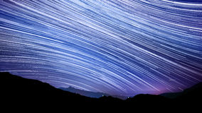 Star trail effect over mountain night sky. Colorful lights royalty free stock images