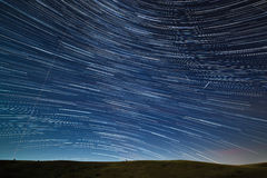 Star trail in the night sky with bright meteors and aircraft ligh. Ts Royalty Free Stock Image