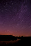 Star trail in the night sky with bright meteors and aircraft ligh Royalty Free Stock Photo