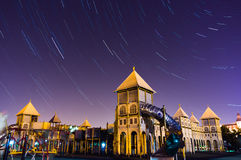 Star trail over city building Stock Photos