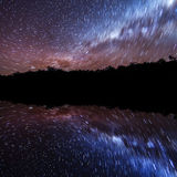Star trails. In the nights sky reflected over water Royalty Free Stock Photography