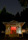 Star trails above a rural Japanese shrine. Star trails make a path in the night sky above a small rural shrine in Japan. The shrine has been painted with light royalty free stock image