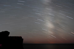 Star trails above the sea cove Stock Photography