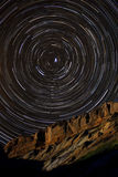 Star Trails around Polaris above a Sandstone Cliff. Stars create arcs around the stationary star, Polaris Royalty Free Stock Images