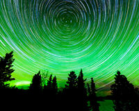 Star trails around Polaris and Northern lights. Astrophotography star trails around the Polar Star or Polaris and green glowing display of Northern Lights or Stock Image
