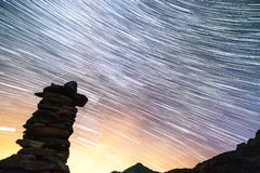 Star trails and balanced rock sculpture in switzerland alps stock photography