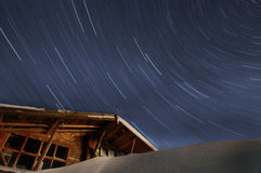 Star trails and buried in snow building Royalty Free Stock Image