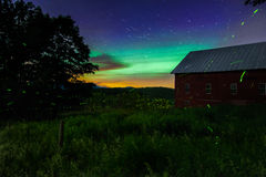 Star Trails, fire flies and northern lights over Farm. Star trails, northern lights and swarms of fire flies illuminate the summer night over a Vermont Farm Royalty Free Stock Photos