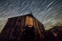 Star trails forming over barn Stock Photos