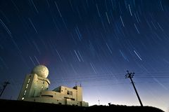 Star trails hovering above a weather radar station stock images