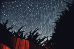 Star Trails. Long exposure of starry night sky framed by trees royalty free stock images
