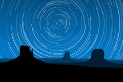 Star Trails at Monument Valley, Arizona, EPS10 Vector. Silhouette of the rock formations of Monument Valley Arizona, USA against a night sky full of star trails vector illustration