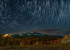Star trails in a mountain village in Romania Stock Photos