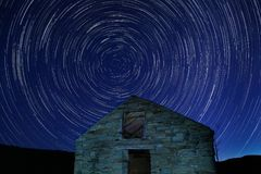 Star trails at night. Old house with star trails in sky at night stock image