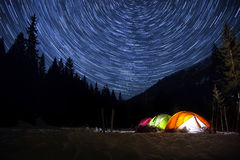 Star trails in the night sky above the tent. Time-lapse. Night camp with illuminated tents in the mountain landscape with star trails in the sky Stock Photos