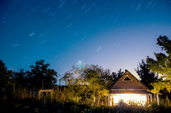 Star trails on the night sky. Country house in the night filled with light and the star trails on the sky above Stock Photos