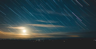 Star trails in a night sky with moon Stock Photo