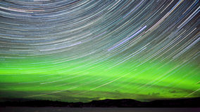 Star trails and Northern lights in night sky. Astrophotography star trails with green glowing display of Northern Lights or Aurora borealis in Yukon Territory Stock Image