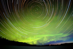 Star trails and Northern lights in night sky. Astrophotography star trails with green glowing display of Northern Lights or Aurora borealis at crack of dawn in Stock Image