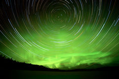Star trails and Northern lights in night sky. Astrophotography star trails with green glowing display of Northern Lights or Aurora borealis in Yukon Territory Stock Photo