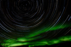 Star trails and Northern lights in night sky. Astrophotography star trails with green glowing display of Northern Lights or Aurora borealis in Yukon Territory Royalty Free Stock Photo