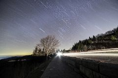 Star trails over country roadway at sunset