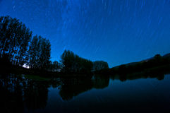 Star trails over the lake. Star trails in a blue night reflected in the lake Stock Photo