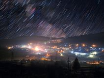 Star trails over mountain town. Night sky with star trails above mountain town Royalty Free Stock Images