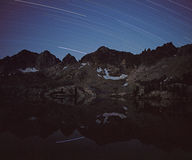 Star Trails over Mountains. Star trails and mountains reflected in lake, long camera exposure at night royalty free stock images