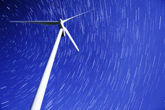 Star trails over a wind power generator Stock Images