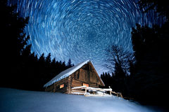 Star trails over wooden house in the winter forest Royalty Free Stock Photography