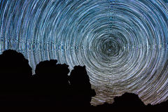 Star Trails with Polaris Star and silhouette rocks stock photo