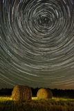 Star trails and wheat field with haystacks Stock Photos