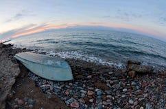 Stara łódź przy Issyk-Kul jeziornym brzeg, zmierzchu krajobraz z pięknymi kamieniami i kipiel, fotografia stock