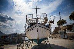 Stara łódź rybacka na brzeg Statek ciągnący na ląd Ukrywa w wiosce Hersonissos na wyspie Crete, Grecja zdjęcia royalty free