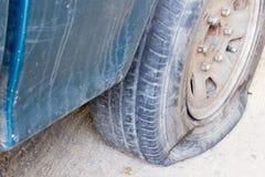 Stara łamająca samochodowa guma, przecieku zielony samochód z kopii przestrzenią guma fotografia stock