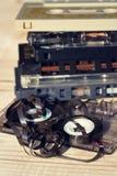 Stara łamająca unwound ścisła kasety taśma dźwiękowa bałaganił up na drewnianym tle Fotografia Stock