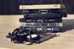 Stara łamająca unwound ścisła kasety taśma dźwiękowa bałaganił up na drewnianym tle Obraz Royalty Free