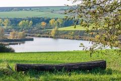 Stara ławka przed pięknym górkowatym krajobrazem z jeziorem obrazy stock