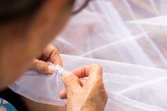 Stara ściekowa kobieta jest szwalnym tkaniną z igłą robić sieci dla Fotografia Stock