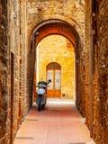 Stara średniowieczna ulica San Gimignano z małym motocyklem, Tuscany, Italia Obraz Royalty Free