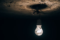 Stara żarówka jarzy się w ciemnej piwnicie elektryczności improwizacja przy budową Obraz Stock