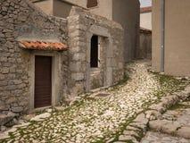 Stara aleja z małymi brukowymi kamieniami i starymi domami w Lubenice Zdjęcia Royalty Free