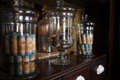 Stara apteka, gablota wystawowa Buteleczki i antyk butelki z różnymi substancjami, medycynami lub cieczami na półce, fotografia royalty free