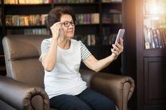 Stara azjatykcia kobieta patrzeje smartphone ekran Obraz Royalty Free