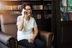 Stara azjatykcia kobieta używa smartphone dla opowiadać Obraz Stock