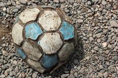 Stara będąca ubranym i drzejąca piłki nożnej piłka na kamiennych otoczakach Zdjęcia Stock