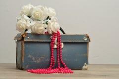 Stara będąca ubranym out błękitna walizka z wiązką sztuczne białe róże i zawiązuje różowych koraliki Obraz Royalty Free
