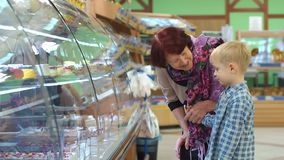Stara babcia z małym wnukiem w supermarkecie wybiera cukierki zdjęcie wideo